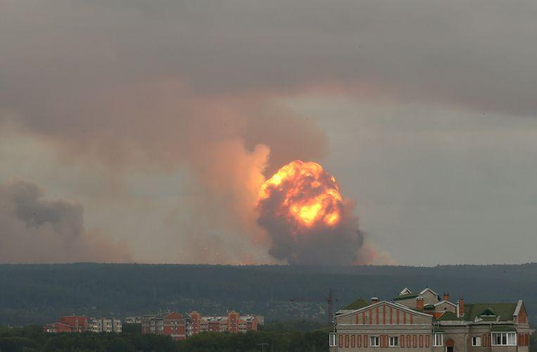 Een enorme vuurbal rijst op boven een wapendepot bij de Siberische stad Atsjinsk waar zich maandag een reeks ontploffingen voordeed. Op het terrein lagen tienduizenden granaten en bommen opgeslagen. Beeld REUTERS