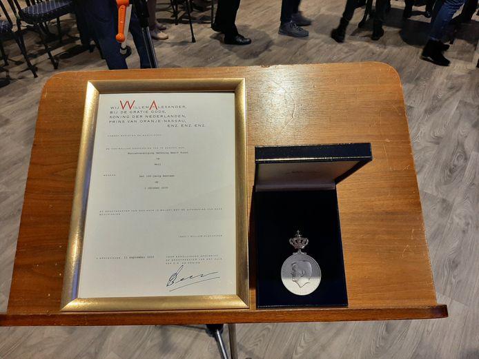 De Koninklijke Erepenning met bijbehorende oorkonde werd uitgereikt door burgemeester Henny van Kooten aan Jos Rooijens, voorzitter van OBK.