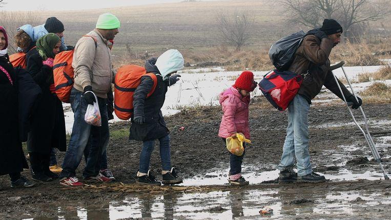 Vluchtelingen ploeteren door de modder op weg naar een tijdelijk opvangkamp in Macedonië Beeld epa