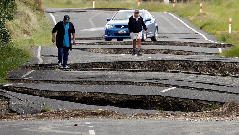 Buurtbewoners bekijken de schade die de beving van zondag aanrichtte in de buurt van het stadje Ward op het Zuidereiland. Beeld REUTERS