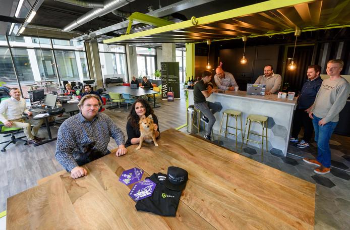 Jamie Maria Schouren en haar compagnon Roland Bastiaansen met hondjes te midden van collega's in het kantoor van Deity.