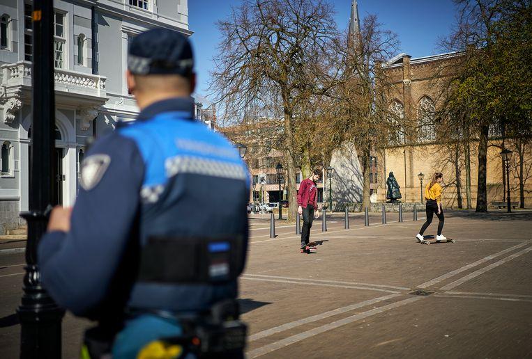 Mensen lopen met een grote boog om elkaar heen, zien Haagse boa's Mounier en Soeris. Beeld Phil Nijhuis