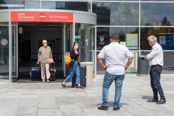Reizigers bij de ingang van de terminal van Eindhoven Airport.