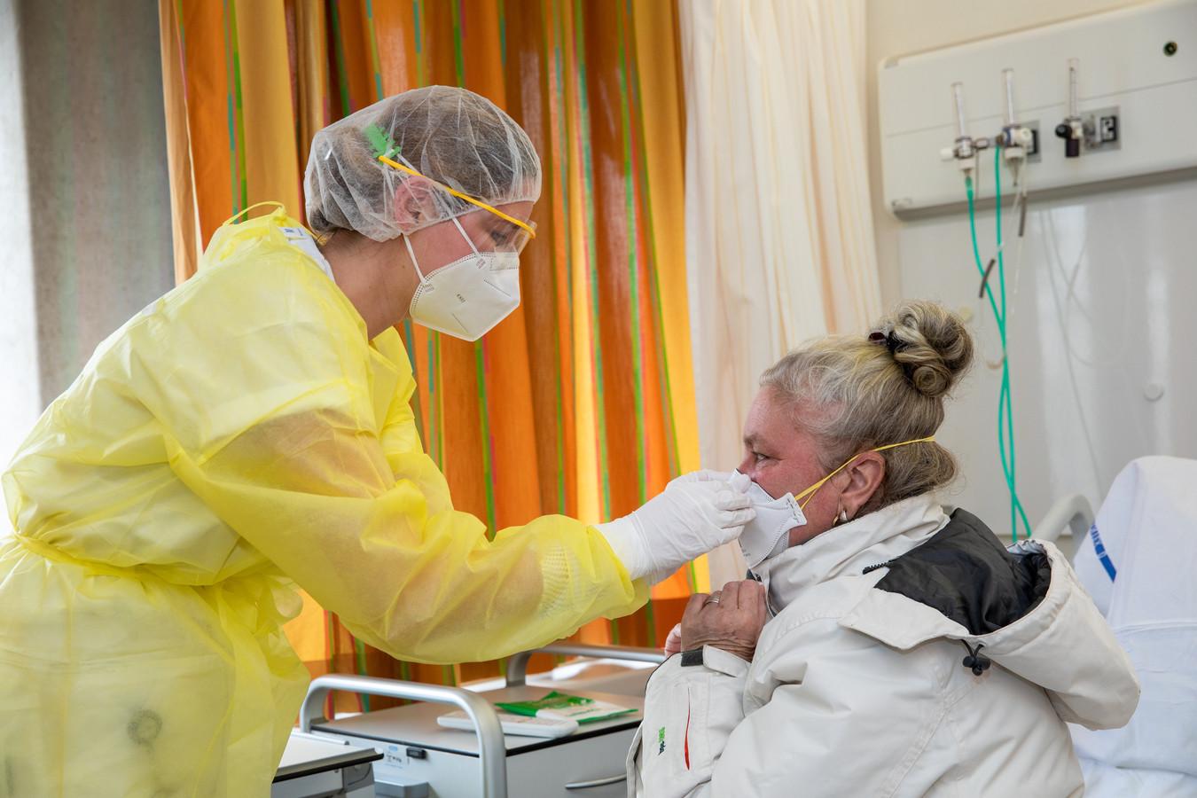 Wendy zet Mieke een medisch mondmasker op voor ze van de corona-afdeling af gaat.