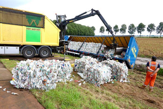 Het plastic wordt uit de vrachtwagen gehaald.