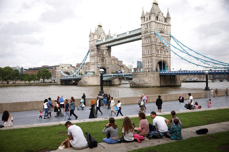 Toeristen en inwoners van Londen kuieren aan de Tower Bridge. Sinds Freedom Day zijn mondmaskers niet meer verplicht in Groot-Brittannië. Beeld REUTERS
