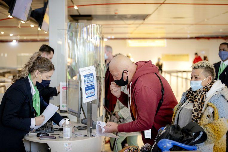 Twee reizigers overhandigen hun negatieve PCR test om in te checken op Schiphol.  Beeld ANP