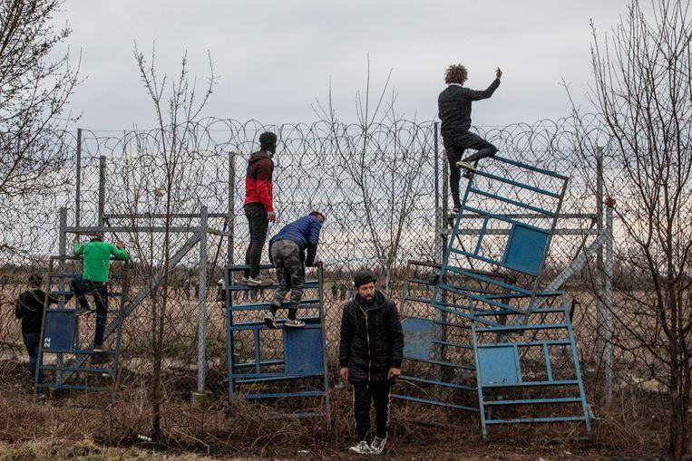 Migranten proberen het grenshek over te klimmen tussen Turkije en Griekenland.  Beeld Getty Images