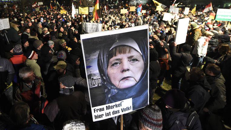 Duitse Pegida-demonstranten tonen een gesluierde Angela Merkel. éHier is het volk.