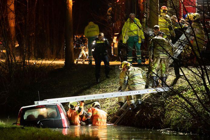 Brandweerlieden helpen een onfortuinlijk echtpaar uit hun auto in de sloot.