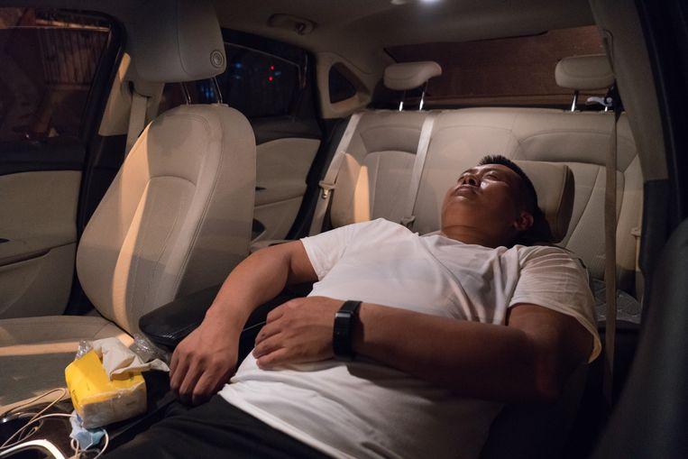 Om 1.00 uur 'snachts doet Mhao Ziwen een dutje in zijn auto. 'Zodra ik ga liggen, val ik in slaap.' Beeld Ruben Lundgren