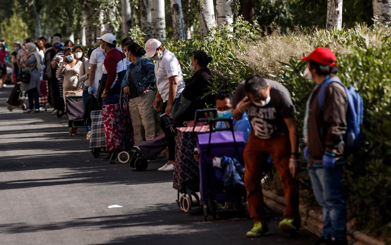 In de wijk Aluche in Madrid staan mensen in de rij voor wat eten. De rij is vaak tientallen meters lang. De hele dag door sluiten er mensen aan.