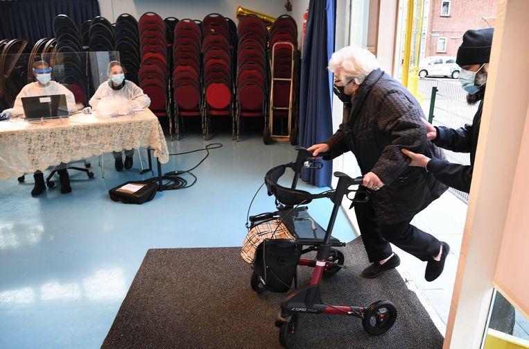 Een oudere inwoner van Charlois wordt door een wijkgenoot geholpen bij de ingang van de testlocatie.   Beeld Marcel van den Bergh / de Volkskrant