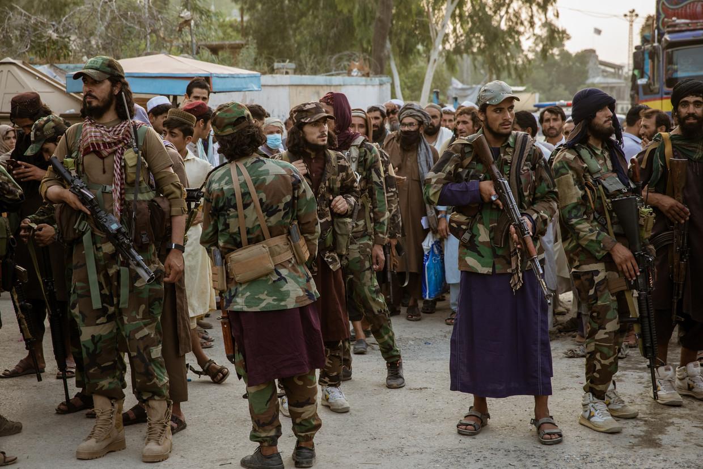 Talibanstrijders controleren mensen die die de grens met Pakistan over willen. Beeld The Washington Post