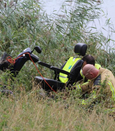 Man rijdt met scootmobiel water Nieuwlandsedijk in