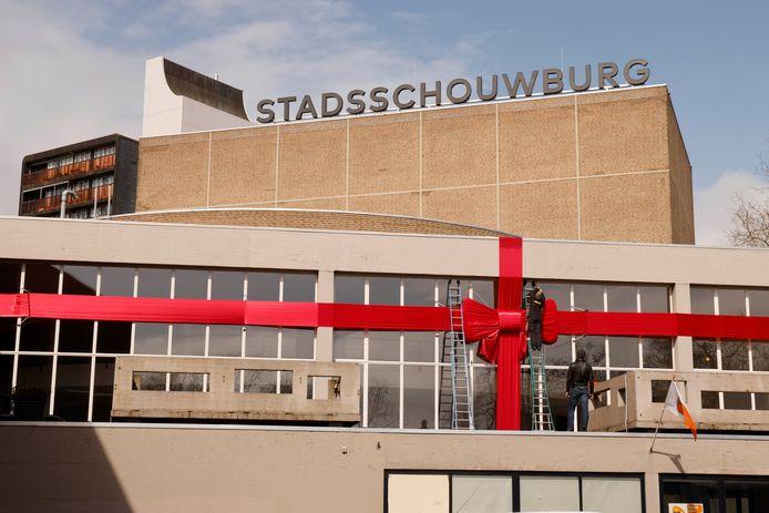 Medewerkers lussen een grote strik om het gebouw van Stadsschouwburg Nijmegen. Anders dan de naam doet vermoeden, heeft het theater een grote impact op de regio.