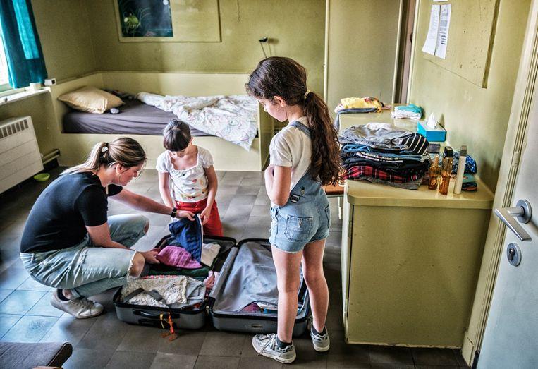 Twee zusjes die net aangekomen zijn, installeren zich met behulp van een medewerker in 't Laar.  Beeld Tim Dirven