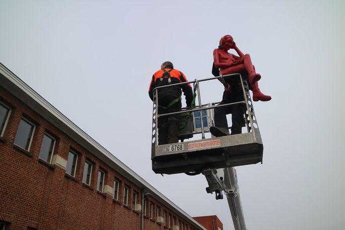 John Meirlaen draagt zijn kunstwerk met een hoogtewerker naar het dak van het zwembad.