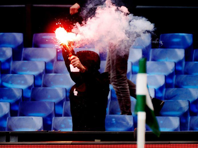 Een supporter steekt een fakkel af in de Kuip tijdens Feyenoord-RKC, een wedstrijd voor de zomer die zonder publiek gespeeld zou worden. Honderden fans drongen plotseling het stadion binnen.