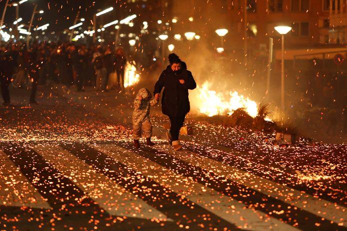 Grote paniek op de boulevard van Scheveningen nadat het vreugdevuur op het strand een zeer grote vonkenregen veroorzaakte die alles om zich heen in de brand stak.