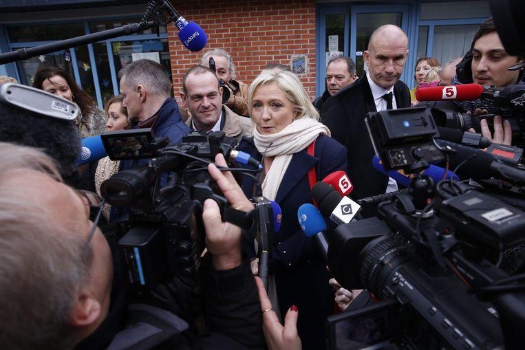 FN-leider Marine Le Pen verlaat het stembureau in Hénin-Beaumont, in de noordelijke regio Nord-Pas-de-Calais. Beeld JULIEN WARNAND / EPA