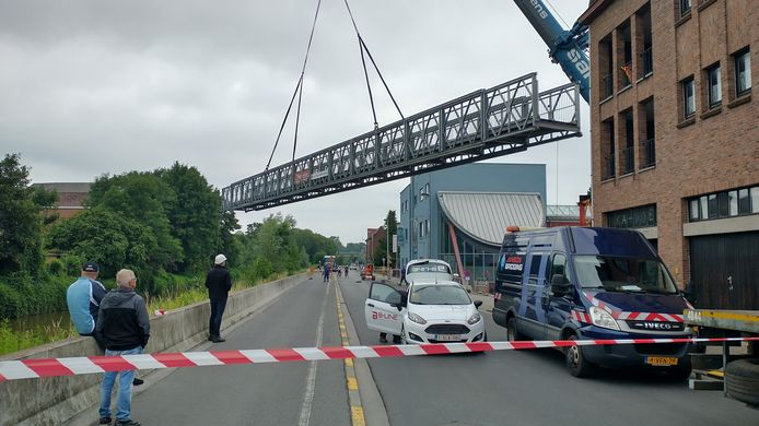Vrijdag werd de tijdelijke voetgangersbrug ter hoogte van jeugdcentrum De Spiraal over de Dender getild.