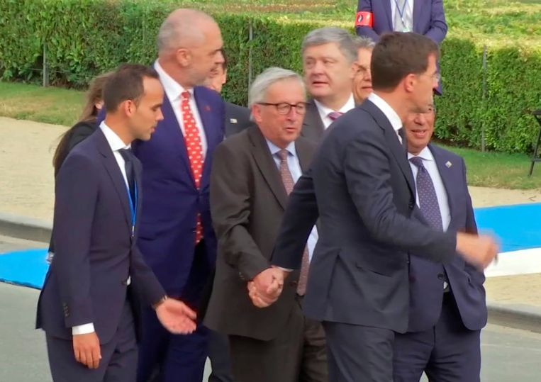 Minister-president Mark Rutte en andere omstanders begeleiden Europese Commissievoorzitter Jean-Claude Juncker woensdag naar een diner op de Navo-top in Brussel. Beeld AP