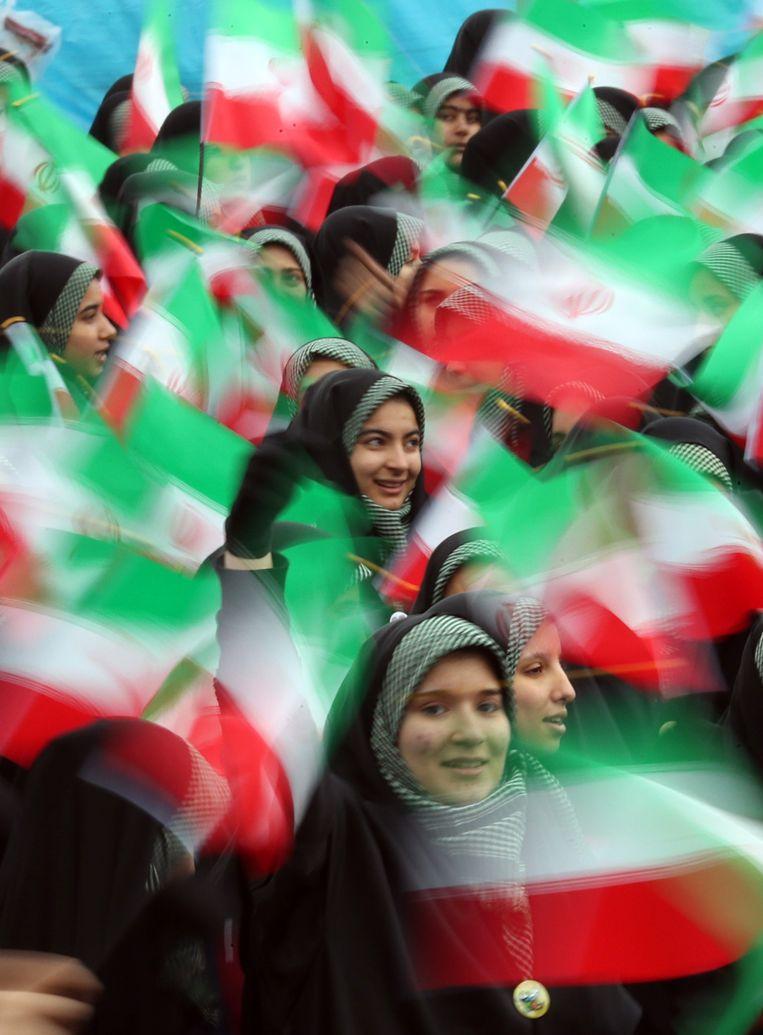 Vrouwelijke studenten zwaaien in Teheran met de Iraanse vlag tijdens de viering van de 40-ste verjaardag van de Iraanse revolutie in 1979.  Beeld EPA