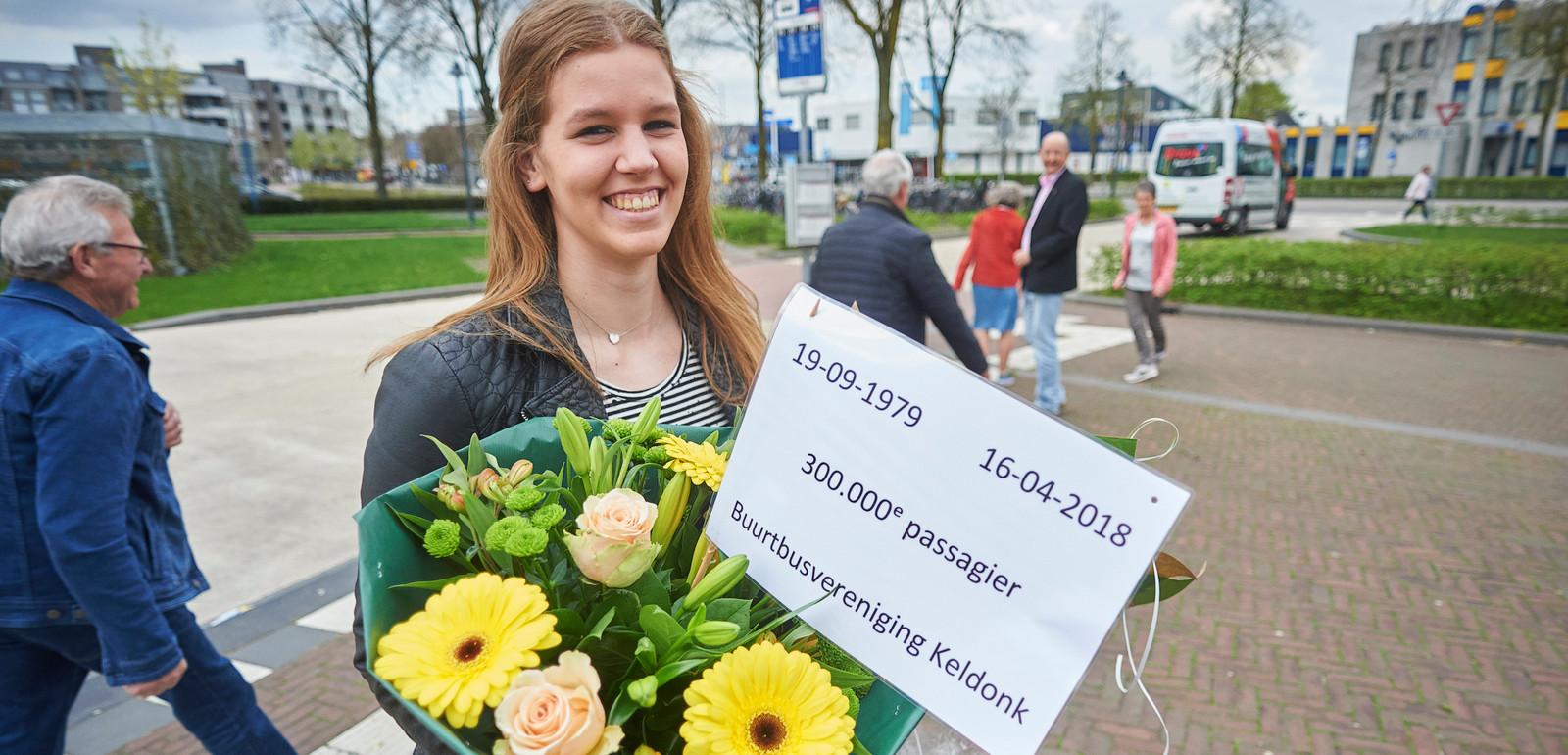 De 300.000ste passagier van de buurtbus, Ilse van Dinter. Vlak nadat ze uitstapte op het busstation te Veghel werd ze gefeliciteerd door wethouder Van Rooijen.  In de achtergrond rijdt de bus weg.