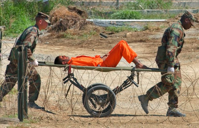Februari 2002: Amerikaanse dienstplichtigen brengen een geketende Guantanamo-gevangene op een draagberrie naar een verhoorplek. Beeld AP