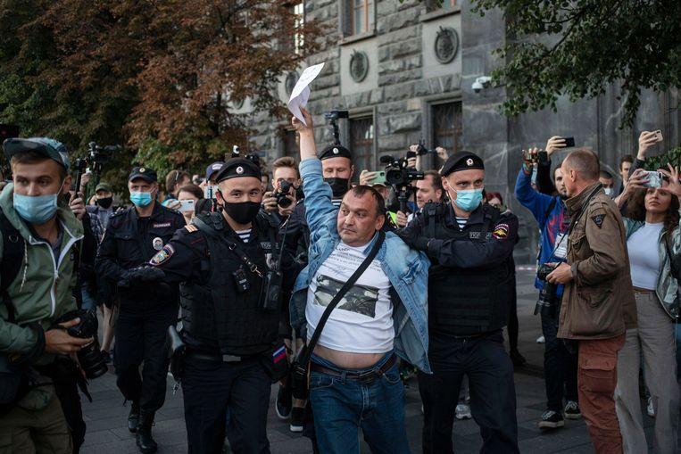 Een actievoerder van de oppositie wordt door de Russische politie weggevoerd.  Beeld AP