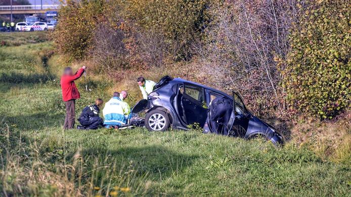 Hulpverleners buigen zich over de auto die in de sloot beland is.