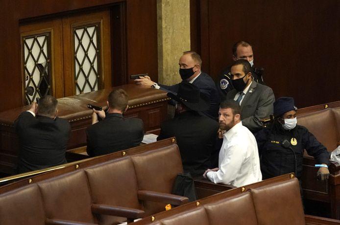 Agenten richten wapens op de deur van de Senaatszaal die dreigt bestormd te worden.