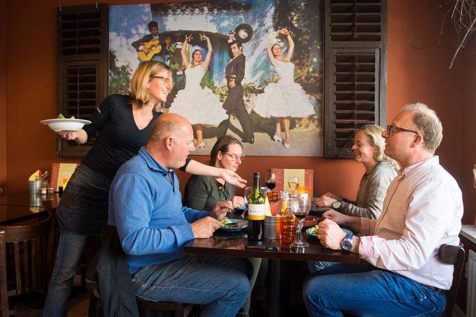 Meddie van den Elshout bedient gasten in haar tapasrestaurant.