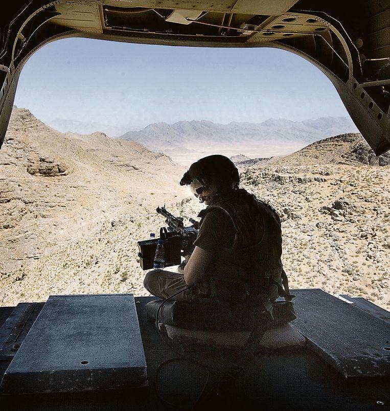 Een boordschutter in een Nederlandse Chinook-helikopter vliegt boven Afghanistan. Beeld Guus Dubbelman / de Volkskrant