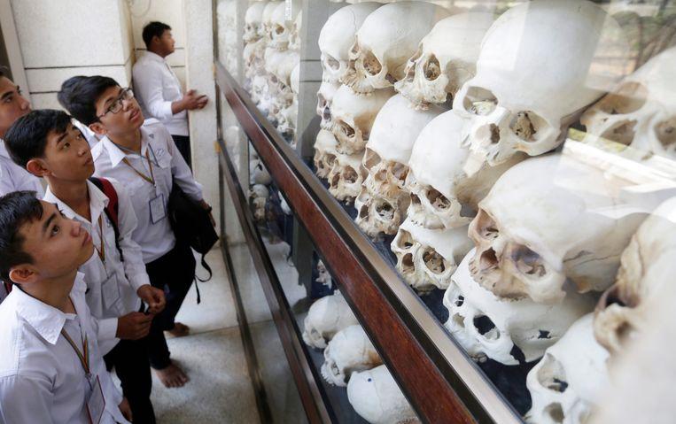 Schedels kijken in het Genocidal Center in Choeung Ek, het grootste Killing Field van Cambodja ten tijde van Pol Pot. Beeld EPA
