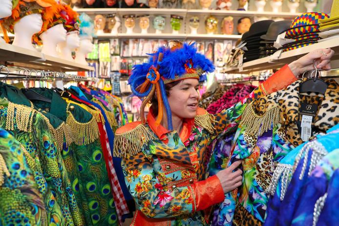 Eigenaresse Eliëtte de Haas van Feestwinkel 't Snabbeltje staat tussen de rekken met gekleurde carnavalsjassen.