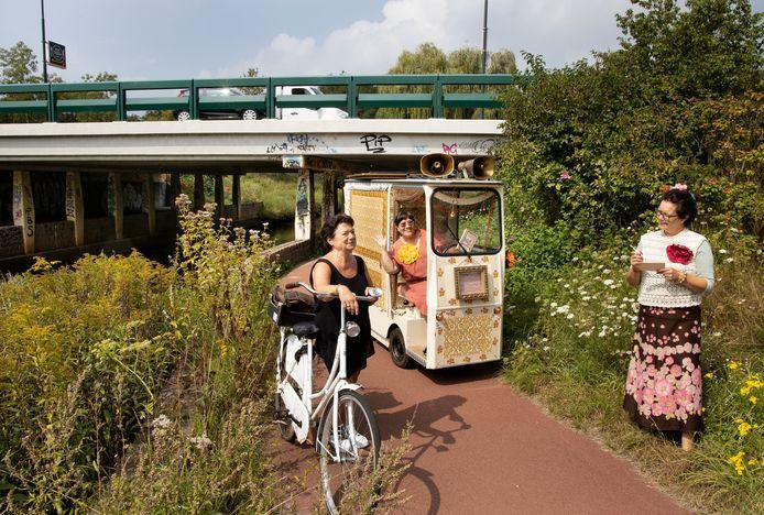 De Koffiedames Wanda Wormser (rechts) en Ellen Schoumacher (in karretje) met fietsster Els van Loon bij één van de tunnels bij De Dommel in Geldrop.
