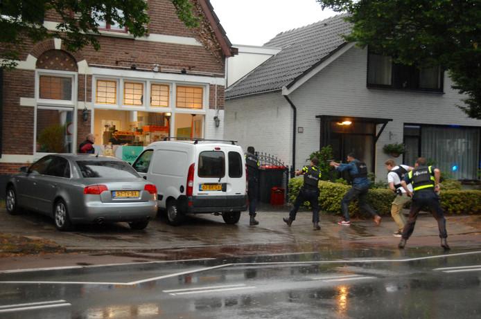 Politie-agenten met kogelwerende vesten houden de verdachte van een overval aan in Velp.