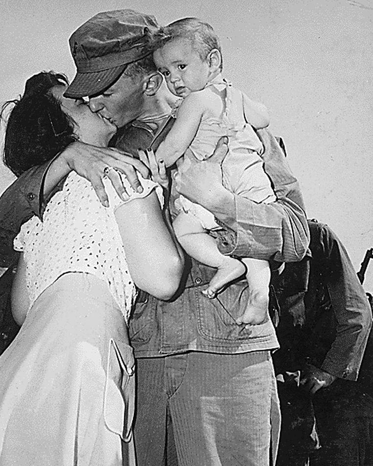 Een Amerikaanse soldaat kust zijn vrouw en kind voordat hij in 1950 afreist naar Korea.  Beeld AFP
