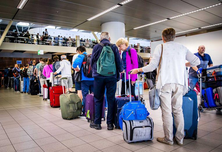Drukte in de vertrekhal van luchthaven Schiphol tijdens het begin van de zomervakantie. Beeld ANP