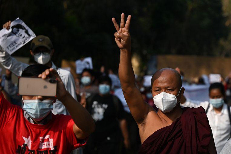 Een monnik in Yangon maakt het inmiddels traditionele gebaar met de drie opgestoken vingers. Beeld AFP