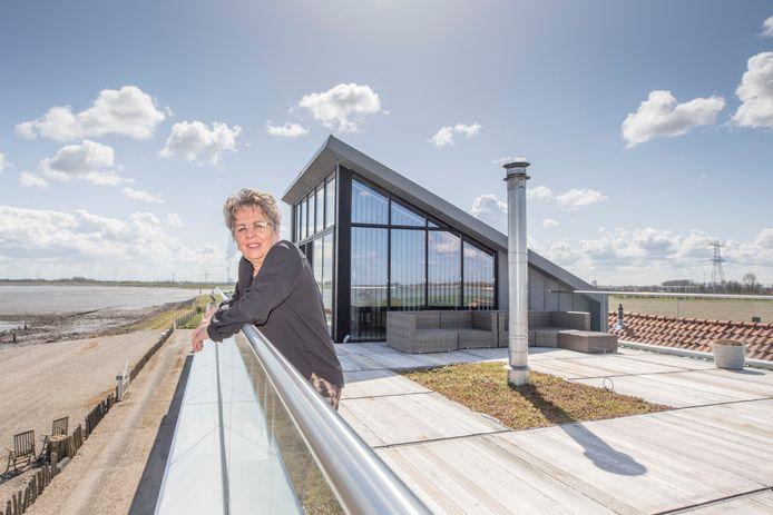 Janneke Vos kan vanaf het dakterras van haar nieuwe huis goed de bouw van de nieuwe 380kV-lijn volgen. Omdat deze lijn rakelings langs het oude huis van de familie Vos komt te lopen, kocht TenneT hen uit.