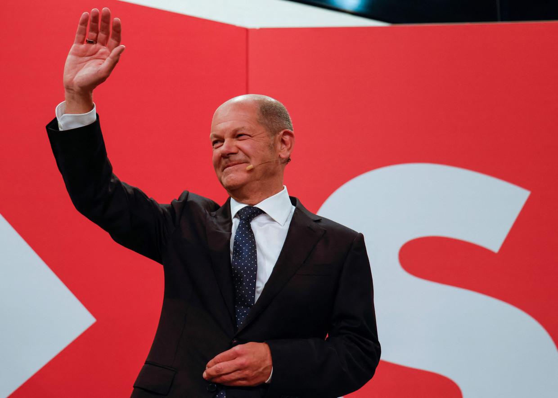 Kanselierskandidaat Olaf Scholz van de SPD zwaait naar zijn aanhang, na het bekendmaken van de eerste exitpolls. Beeld AFP