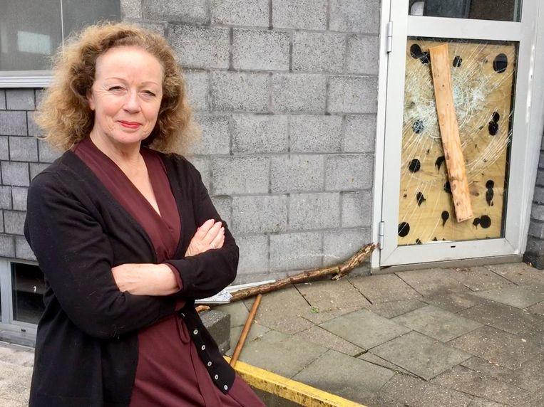 Directrice Marina Stockx voor een kapotgeslagen deur.