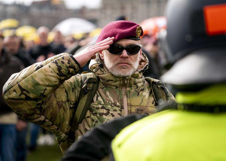 Een demonstrant met een baret op salueert tegenover een politieagent van de Mobiele Eenheid. Beeld ANP