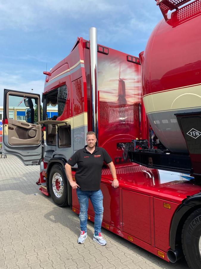 Geoffrey Vermeulen bij 'zijn' Scania. Op de vlakke achterkant, de afbeelding van een korenmolen in een graanveld.