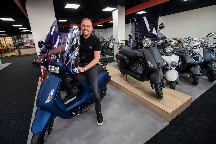 Armando Muis op een scooter in zijn nieuwe winkel in Apeldoorn.
