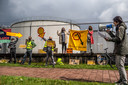 """Actievoerder Erik Lu hanteert de megafoon bij de demonstratie bij Shell in Arnhem. ,,We staan vandaag stil bij de schade die Shell aanricht en nog van plan is om aan te richten tot elke druppel olie uit de grond is gehaald."""""""