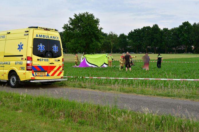 Hulpverleners houden een scherm rond het lichaam van de verongelukte paraglider.